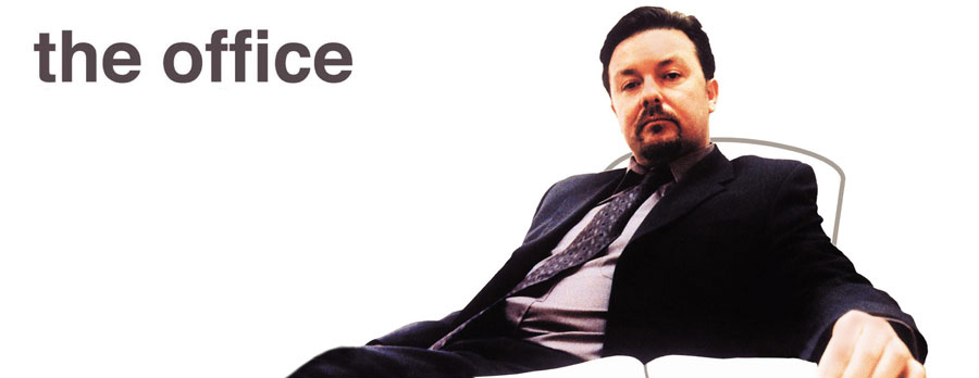 Iconic photo of David Brent (Ricky Gervais) sat at desk