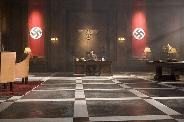 Adolf Hitler (Albert Welling) at the desk in vast office