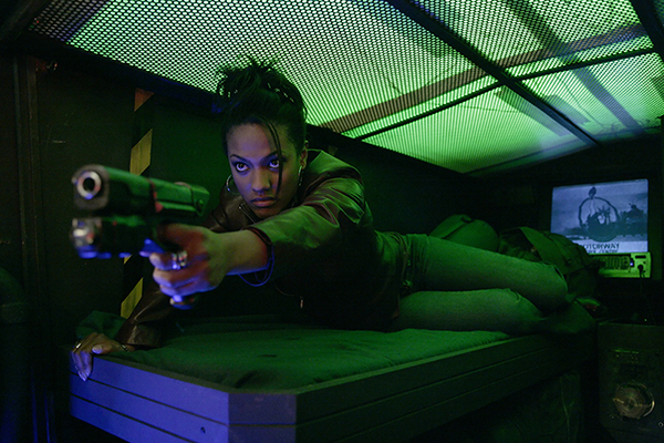 film still of Martha (Freema Agyeman) raising gun from couch