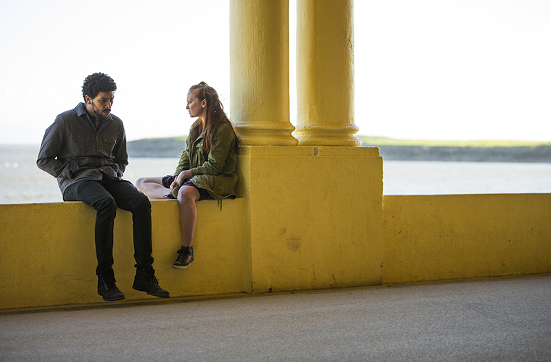 TV series Oridinary Lies 2 - Toke (Joel Fry) & Chrissy (Ella Peel) sat on yellow wall by sea talking
