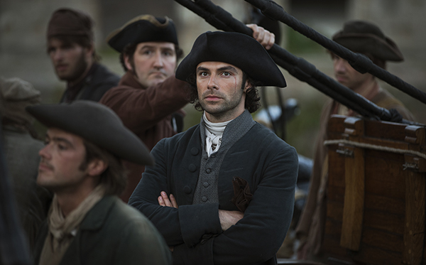 Poldark (Aiden Turner) stands on deck of ship with crew around him